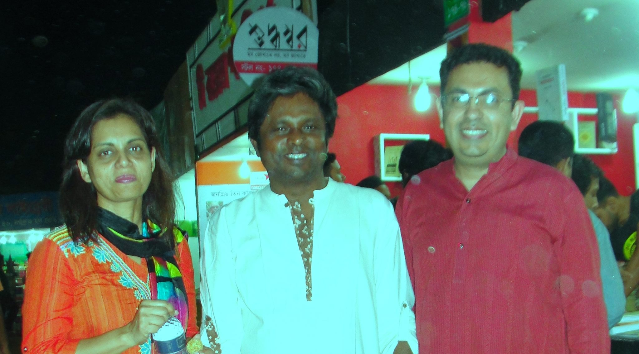Ahmed Rashid Tutul (centre) at his publishing house book stall at the Dhaka International Book Fair, 26 February 2015. This is the night Avijit Roy (right) was murdered, and Roy's wife Rafida Ahmed (left) was seriously injured.