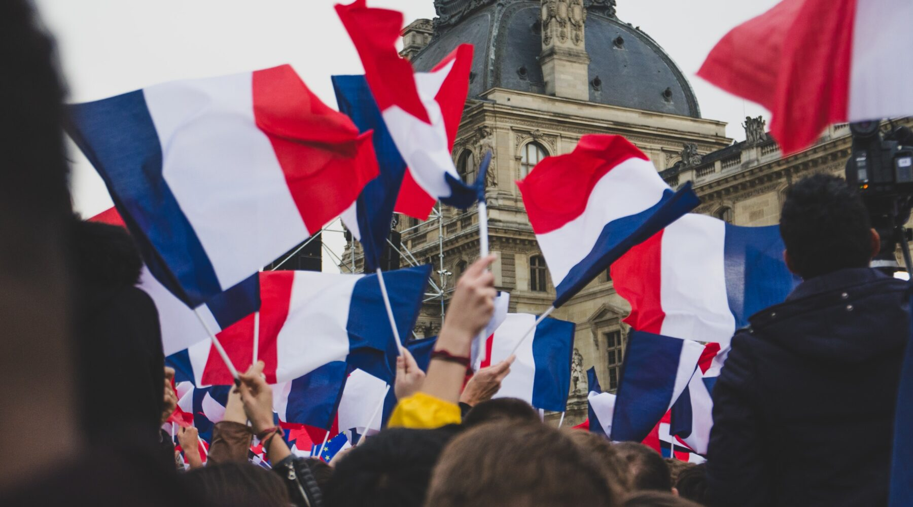 People outside the Louvre waving french flags